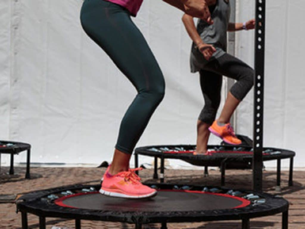 A mother and daughter preparing to do some cool trampoline tricks.