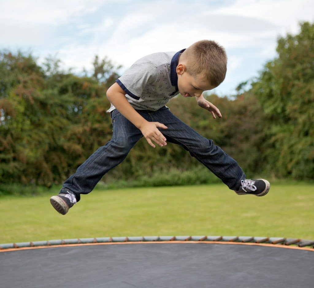 Little boy is bouncing after jumping at the trampoline