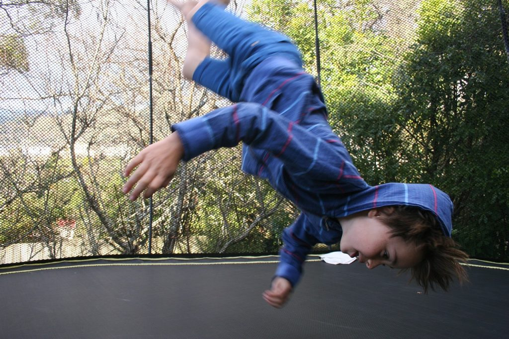 child tumbling on trampoline