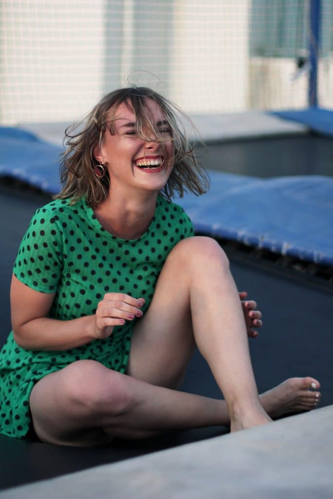 woman laughing on trampoline