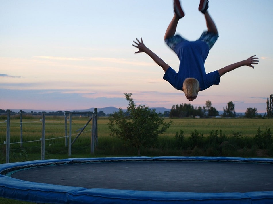A boy doing a Front Flip as  trampoline tricks