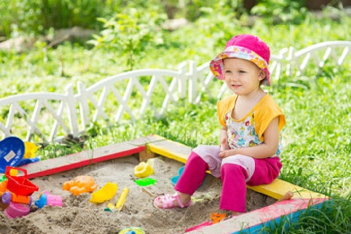 a kid plays on a sandbox as backyard games