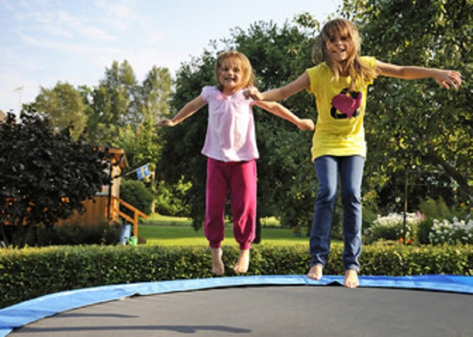 two girls doing trampoline tricks