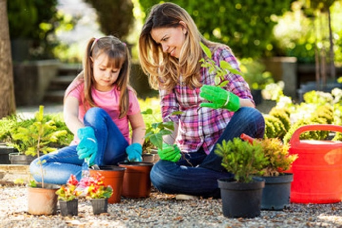 Mother and daughter planting flowers together as backyard games