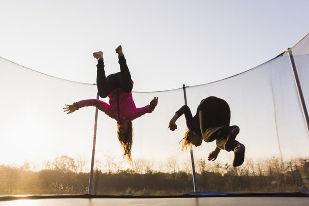 two girls jumping trampoline at sunset