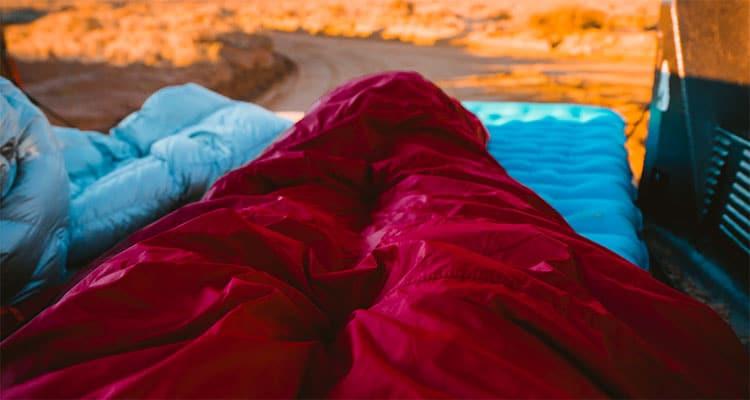 person in sleeping bag overlooking rock