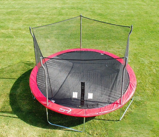 red trampoline in a green grass