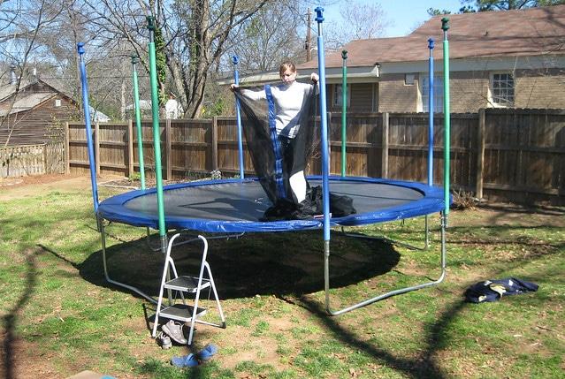a woman installing a trampoline net