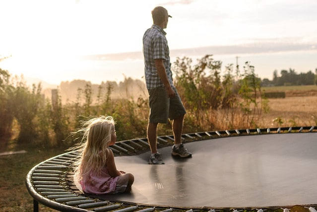 A father and her daughter watching their surroundings in a Trampoline