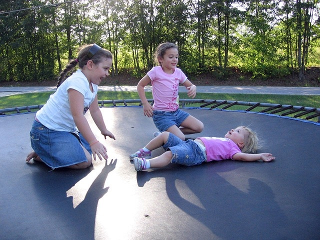 3 little girls are playing at the trampoline