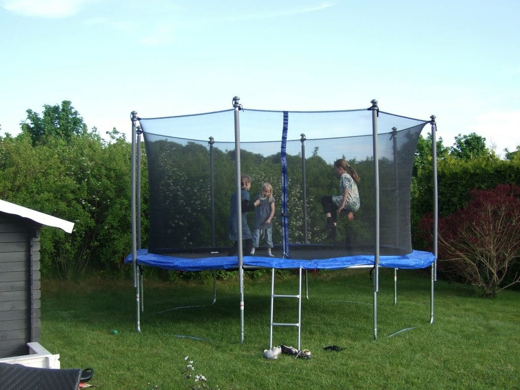 Children are jumping inside the trampoline with net