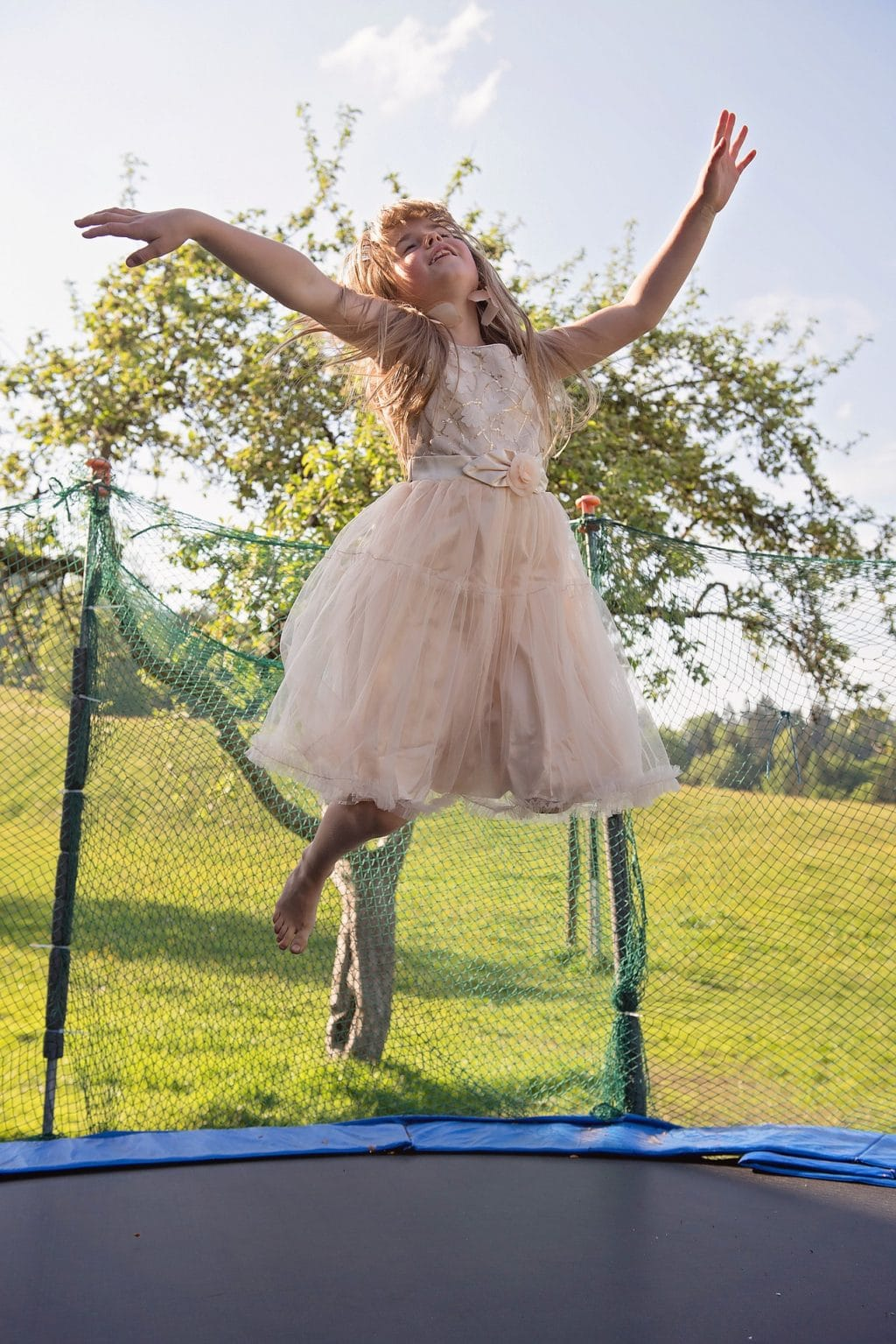 Little girl wearing a fairy costume is jumping at the trampoline and act like a flying fairy